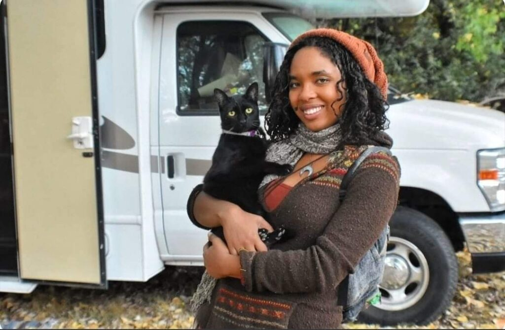 Young woman stands in front of her Class C RV holding her black cat