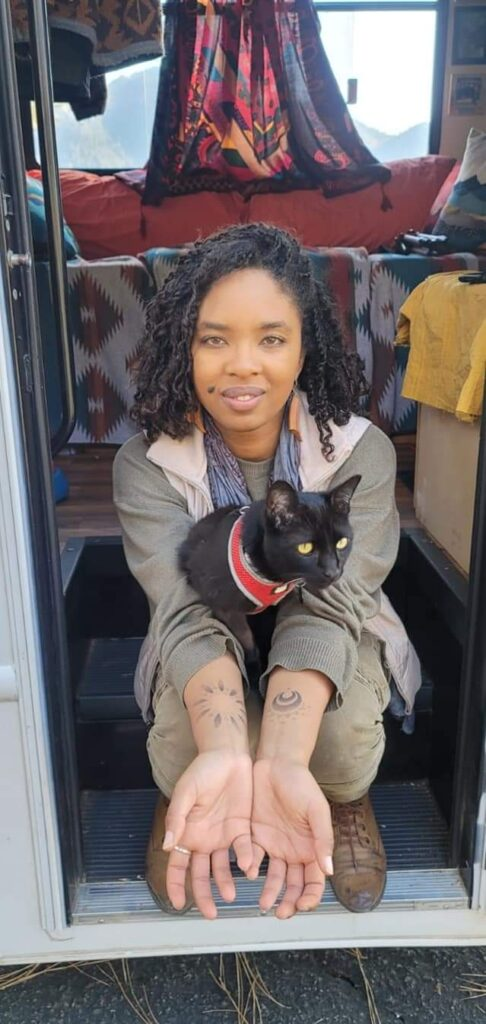 Young woman sits on the steps of her RV with her cat on her lap