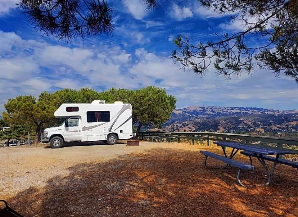 Class C RV parked with mountains in the distance