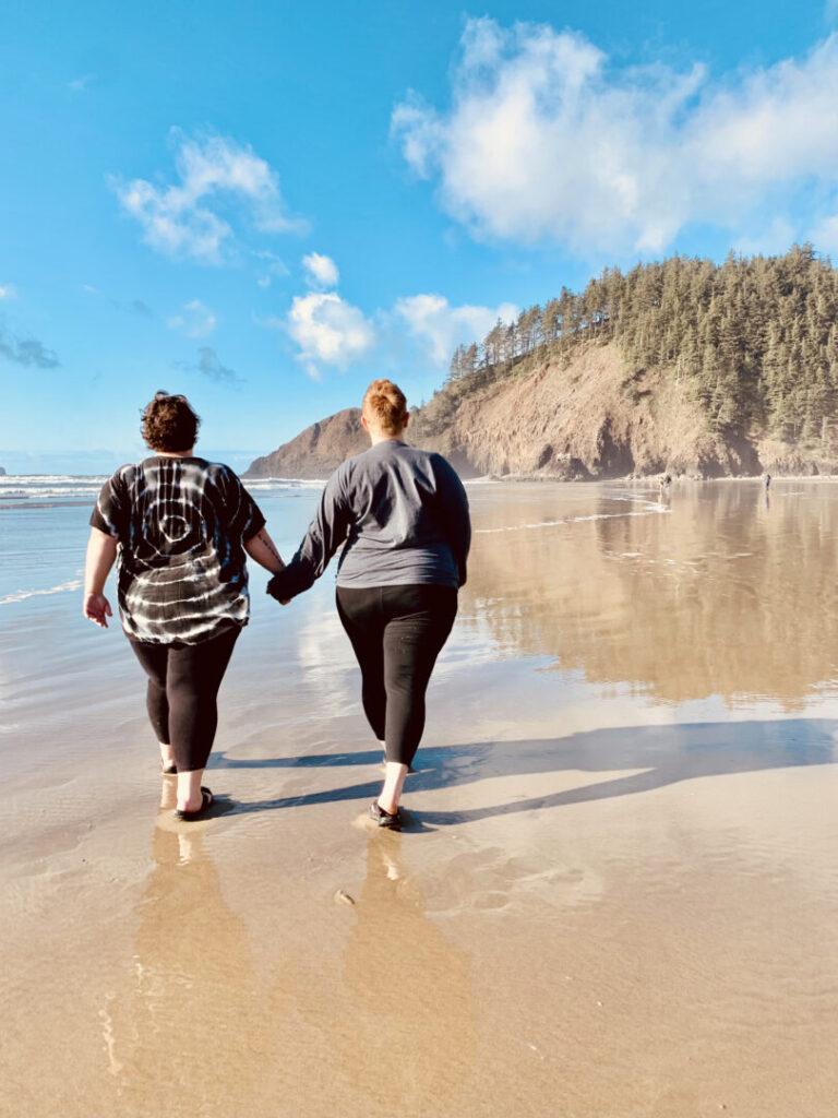 Women hold hands and walk along beach