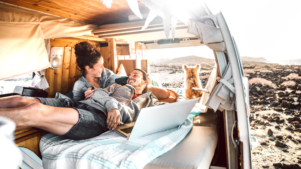 Young couple and their dog relax in campervan
