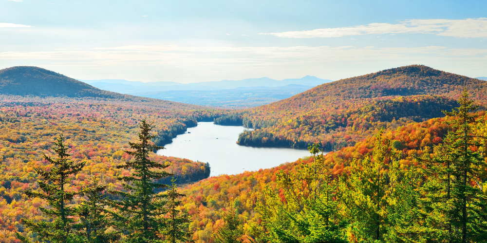 A lake sits in the middle of a valley full of autumn foliage, under a cloudy blue sky.