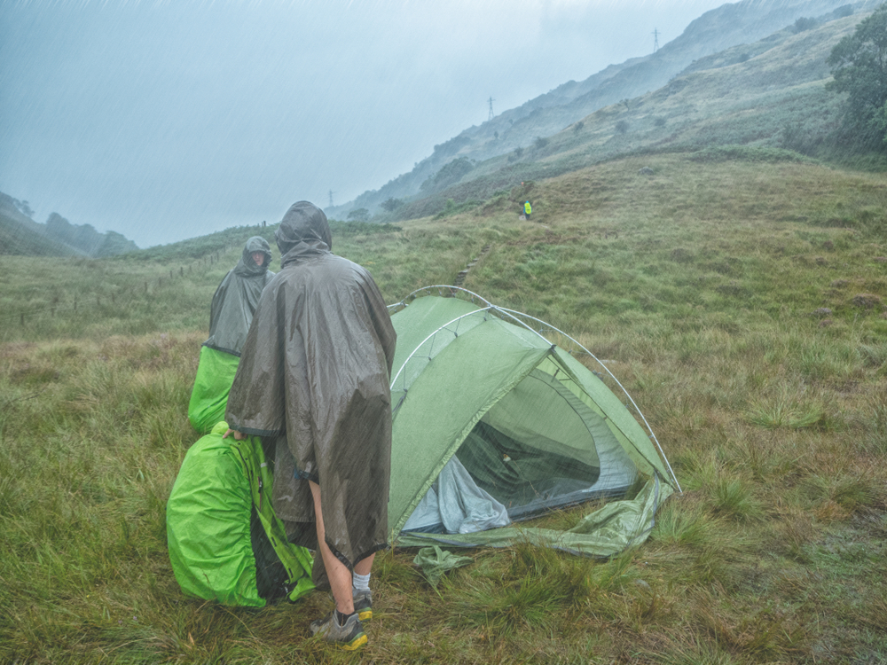 two people with their tent in the rain