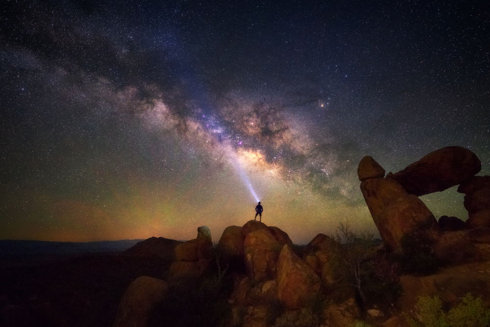 A person standing on a rocky hill looks up at the night sky, illuminated by a headlight, which is a stunning view of the Milky Way.