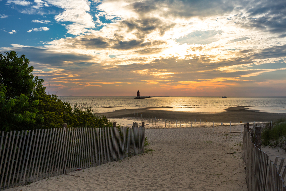 A beach path lined with a short wooden-post fence and green vegetation leads out to a breakwater, the sky lit up with the setting sun and a lighthouse visible in the distance