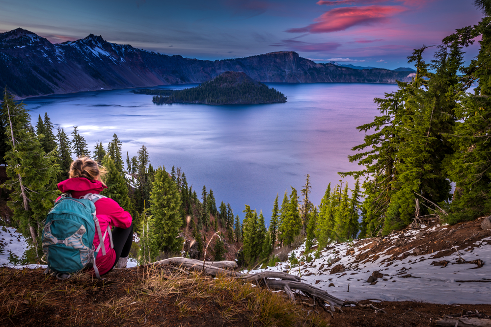A hiker with a pink jacket and blue backpack sits on the ground, looking out over a large mountain lake with an island jutting out of the water. The sunset paints the sky and water pink and purple.