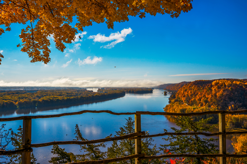 An overlook with a wooden guardrail stands above the Mississippi river, the trees turning autumn colors.