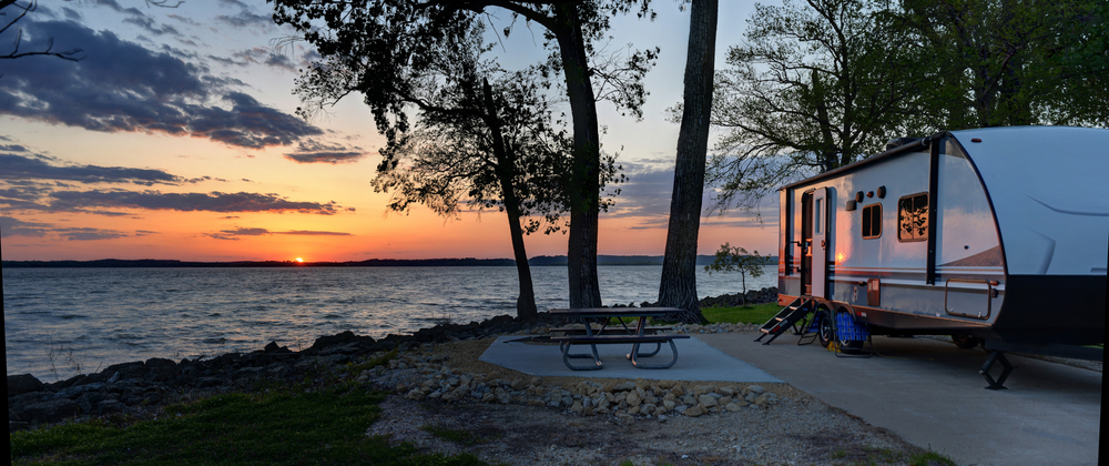 A large RV parked in a concrete camper spot next to a picnic table, set on the shore of a bay of water.