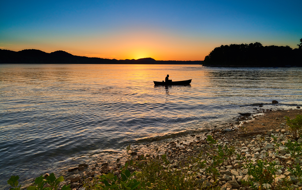 A canoeist on a lake is silhouetted by the setting sun, turning the sky orange. The lake shore is rocky and covered with grass.