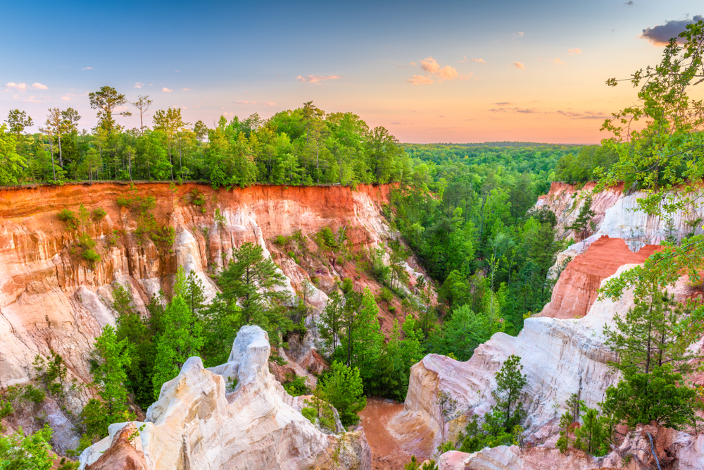A canyon made up of red and white rock formations, with verdant green trees growing in the base and around the rim of the formations. The sunset tinges the sky pink and orange in the distance.