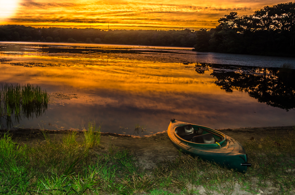 A kayak sits on the grassy shore of a lake colored orange and reflecting the clouds at sunset.