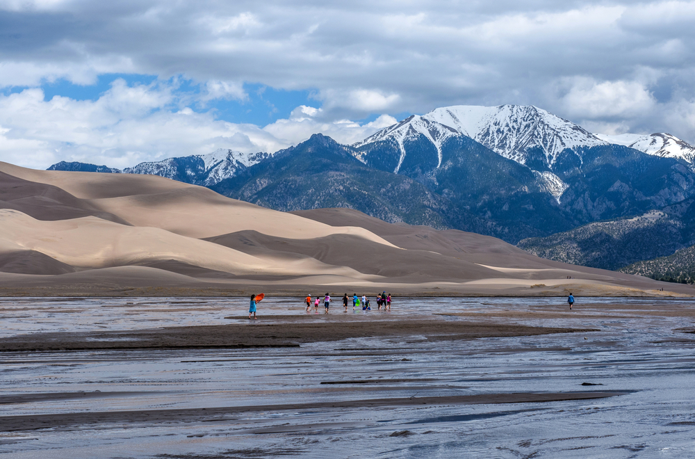 Great Sand Dunes National Park & Preserve, Colorado, USA - May 06, 2016: A group kids are playing in Medano Creek at the base of sand dunes and snow-capped peaks as spring clouds passing over.
