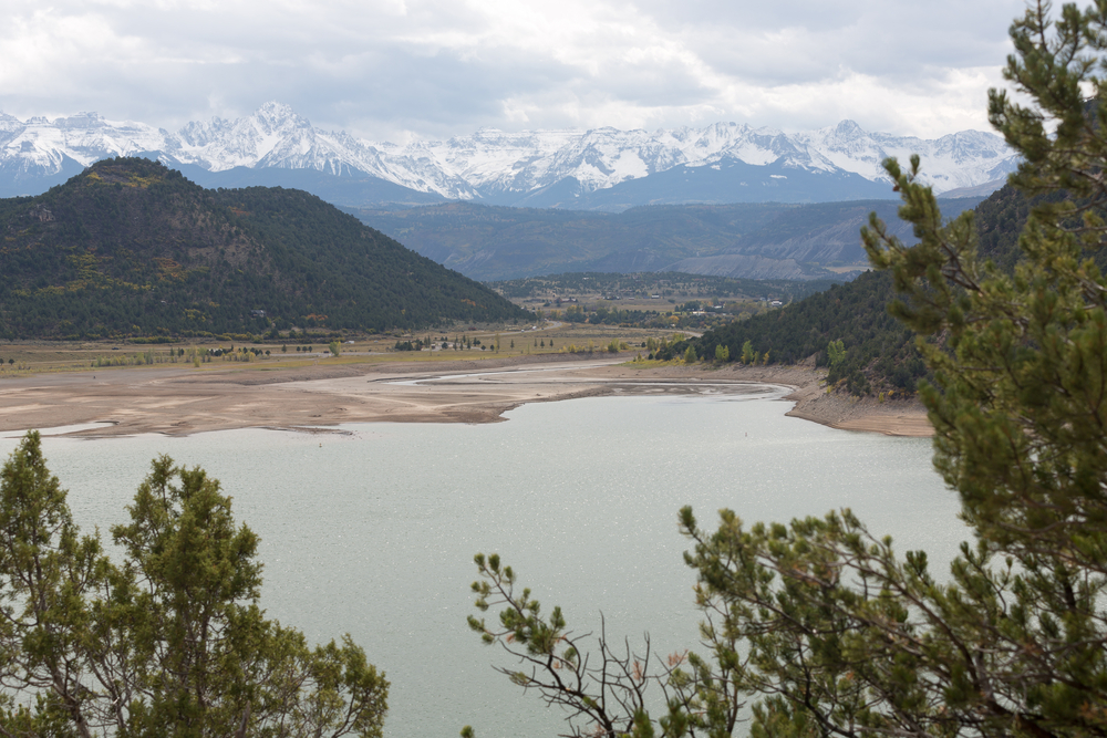 Ridgeway Reservoir and The Sneffels Range in a bright day light misty cloudy sky as seen from Ridgway State Park near Ridgway, Colorado, USA.