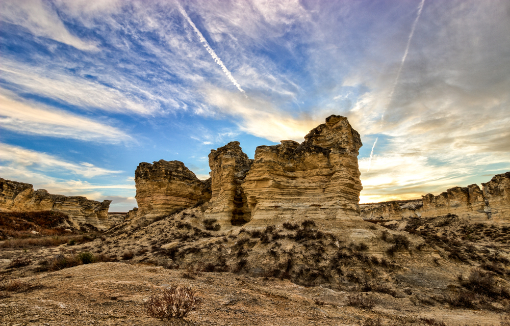 A unique rock formation with scrubby underbrush sits in a rocky plain,