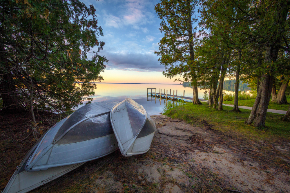 Three aluminum canoes rest on the shore of a lake, off the side of a dirt path, surrounded by dense trees.