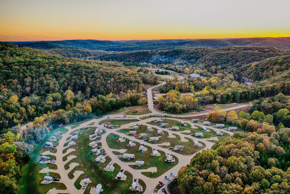 An aerial view of a large RV park with many sites nestled in a forest valley.
