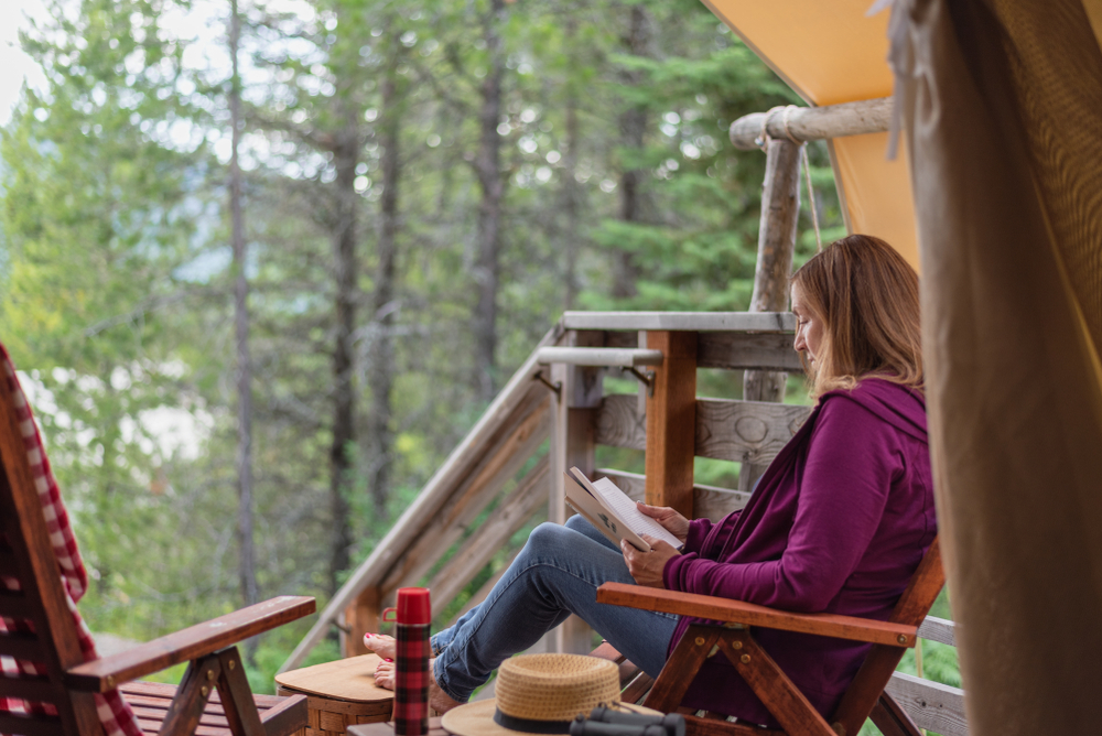 A woman in a purple jacket and demin jeans sits in a wooden porch chair reading a book, surrounded by a forest of thin trees.