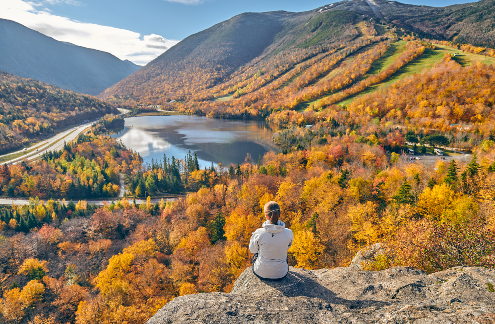 A woman sits on a granite cliff overlooking a forest in autumn covers surrounding a lake at the foothills of a mountain.