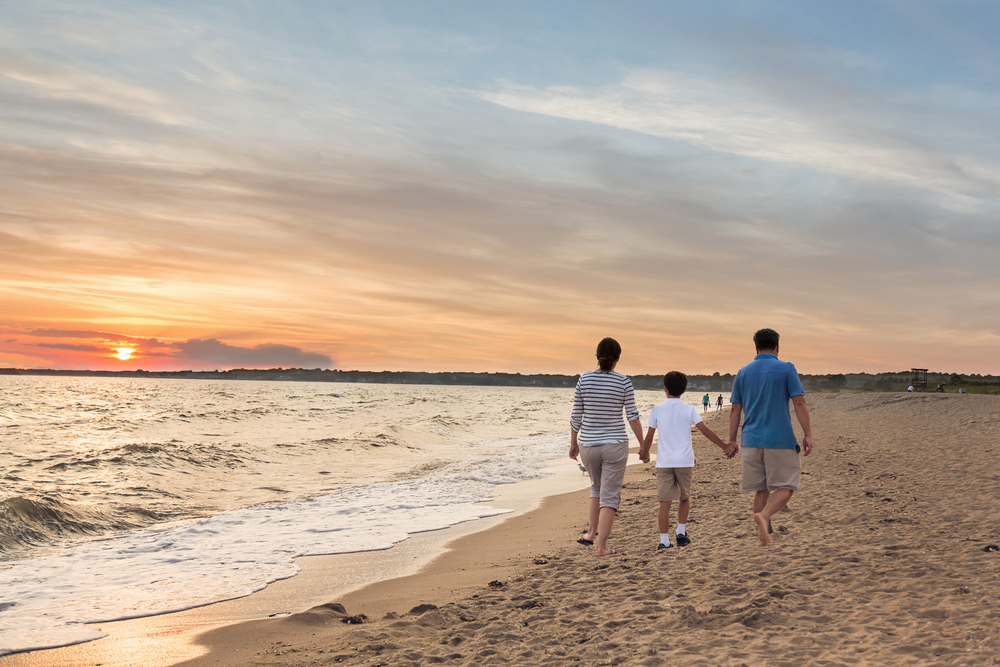 a family enjoying a stroll on the beach at sunset