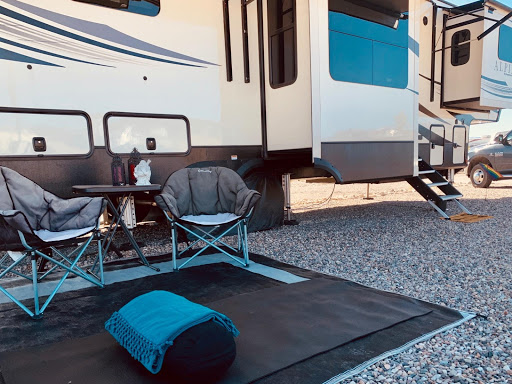 Yoga mat and chairs set up outside a fifth-wheel trailer
