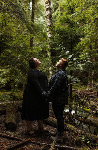 Couple holds hands and looks upward in the middle of the woods