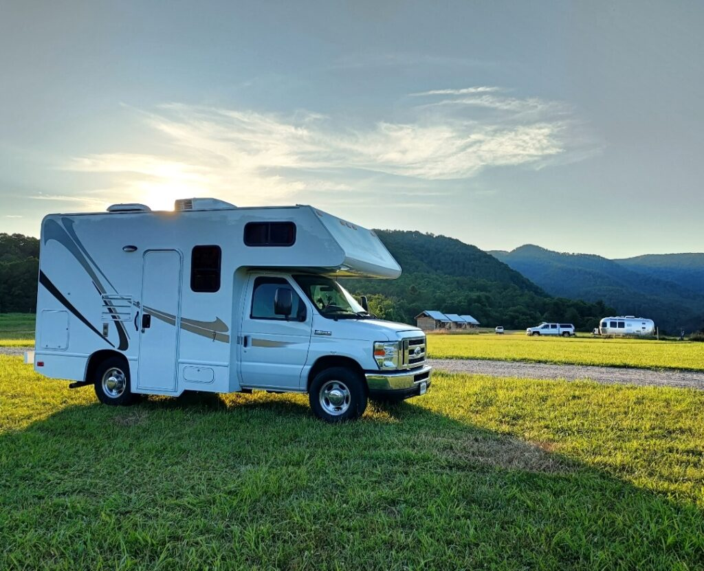 Class C RV parked in a grassy field
