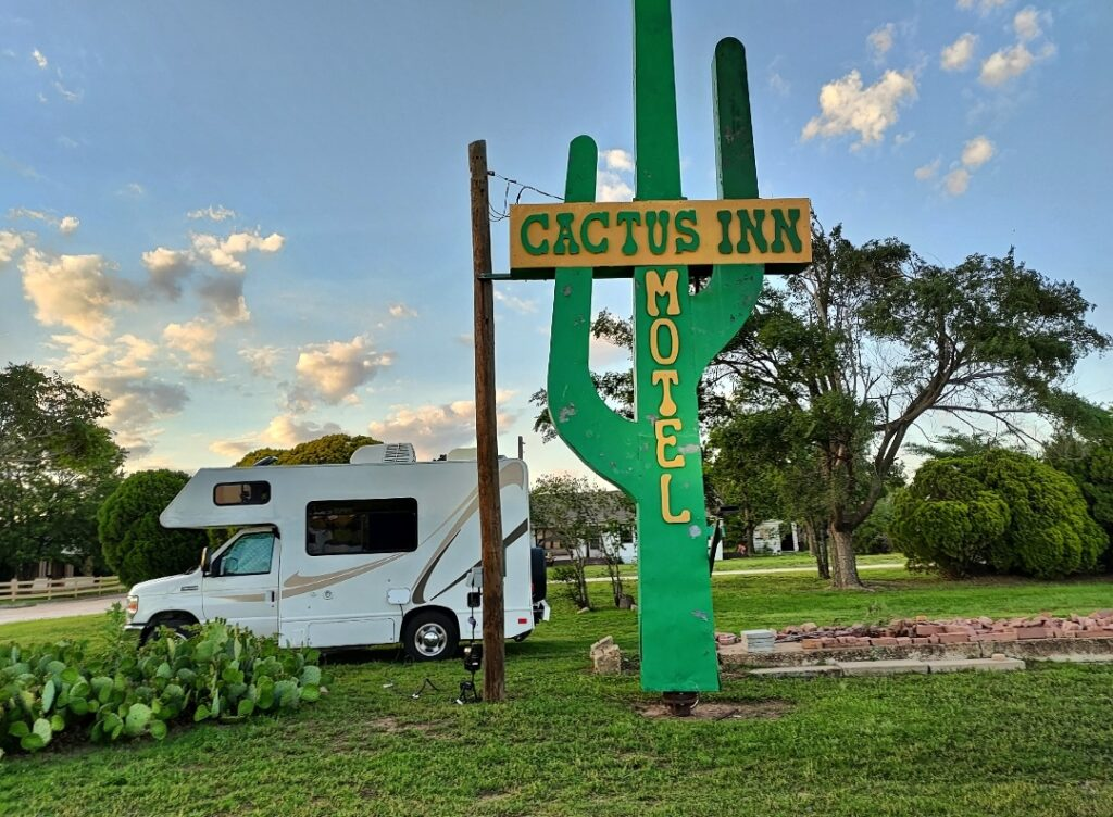 Class C RV parked next to a sign reading Cactus Inn