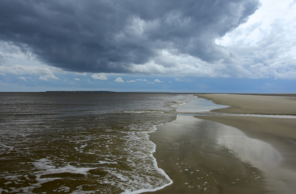 stormy skies, waves and tidal flats at low tide on jekyll island, georgia