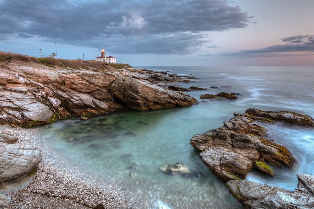 Waves roll towards a rocky beach shore, a lighthouse sitting on the beach in the distance.