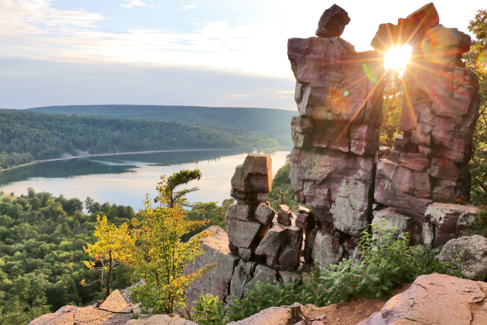 The sun shines through a unique rock formation atop a rocky cliff, looking out over a forest and lake.
