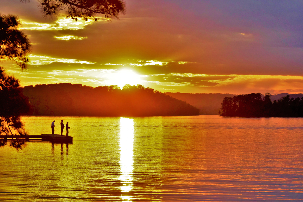 Three people fish off a dock in a lake, turned gold by the rising sun.