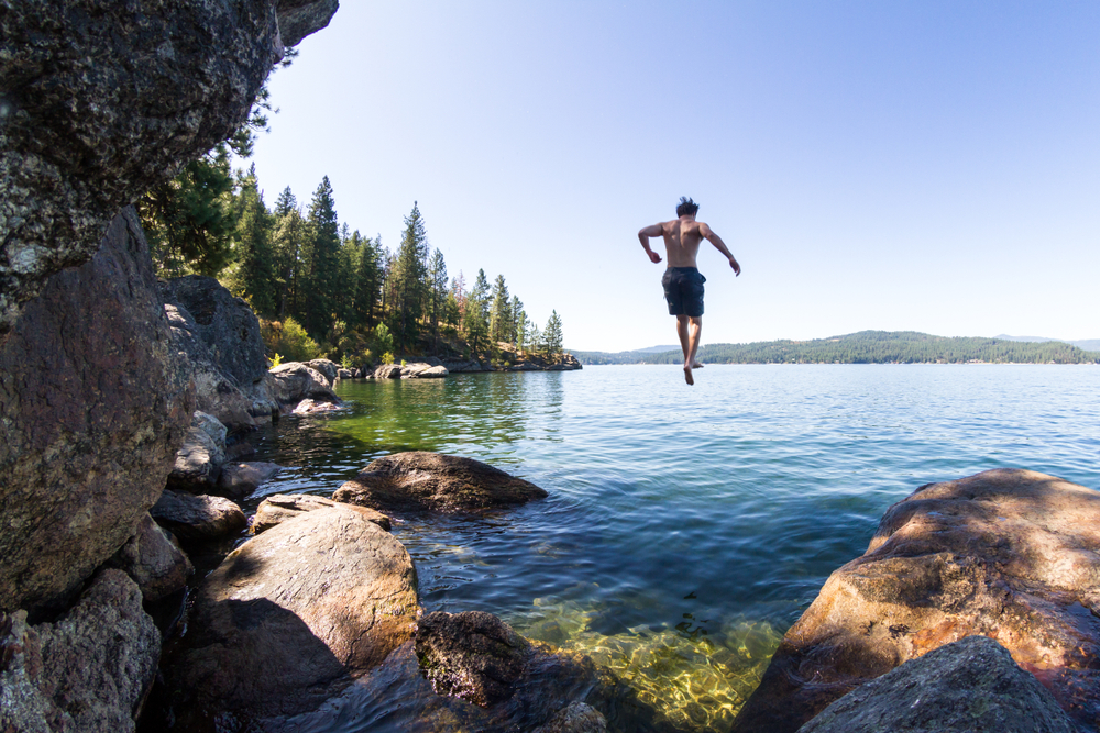 young man jumping of a rocky cliff in Tubs Hill in to Coeur d' Alene Lake in Northern Idaho