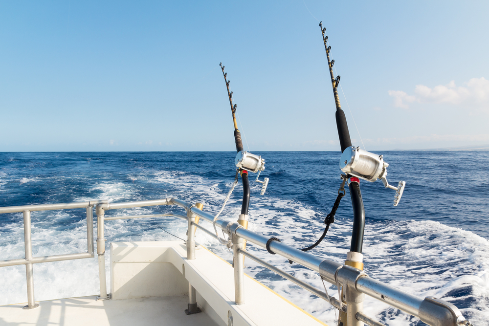 two fishing poles secured to rails on a boat sailing through open ocean waters.