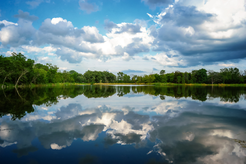 A calm lake reflects fluffy clouds and the surrounding green forest.