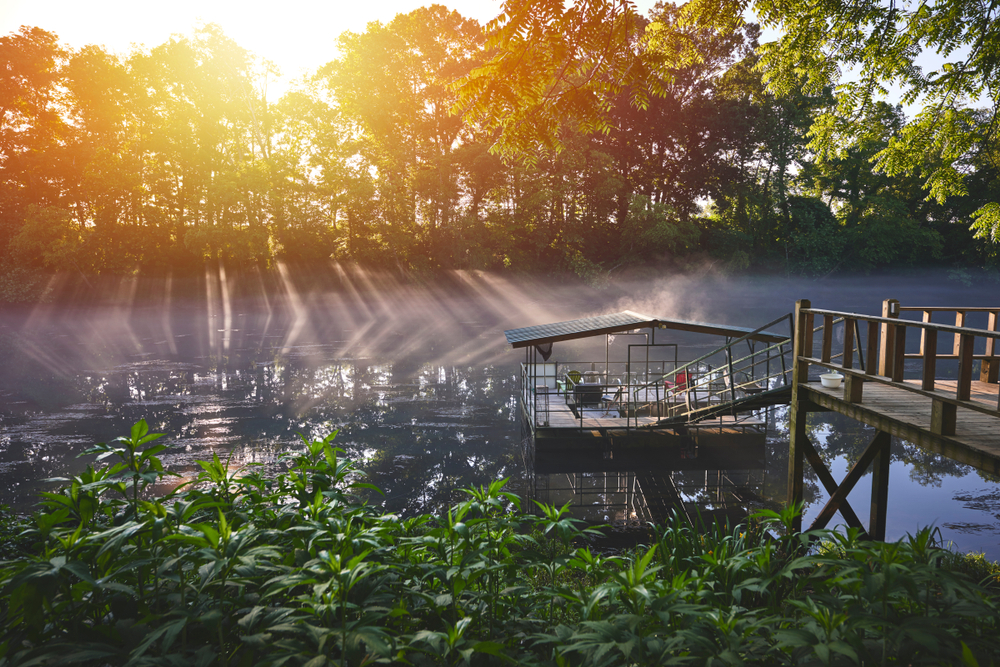 The rising sun burns away the fog over a river dock with seats.