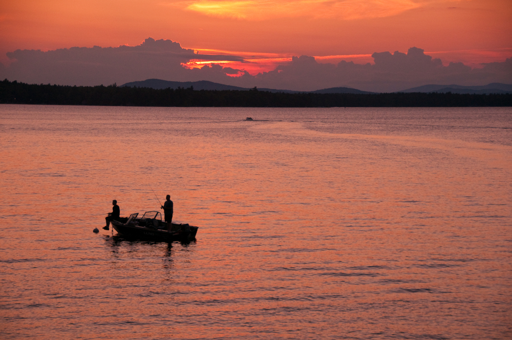 Two people on a boat in the middle of a large, calm lake at sunrise.