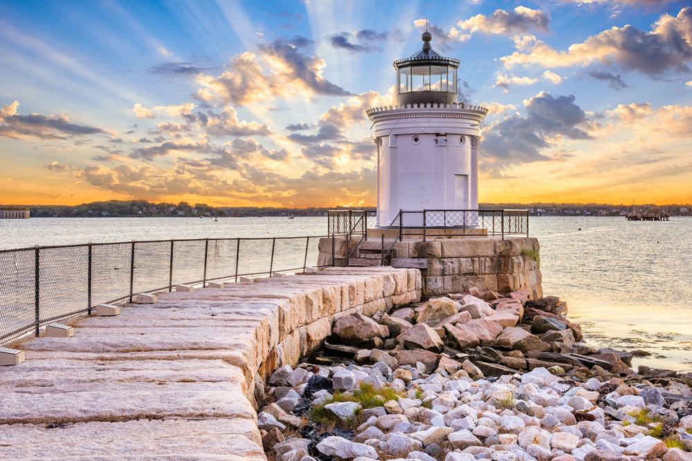 A breakwater on a shore, with a tall lighthouse at its edge. Sunshine peeks through the clouds.