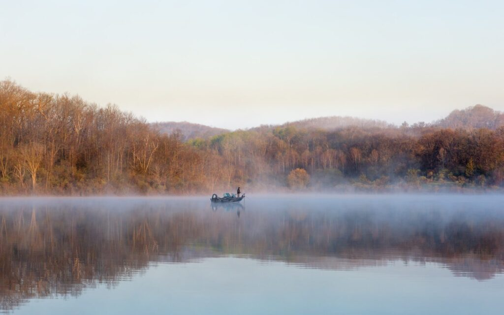 A man stands on a boat in the middle of a calm lake, as fog lifts from the surface of the water. The lake is surrounded by autumn-colored trees.