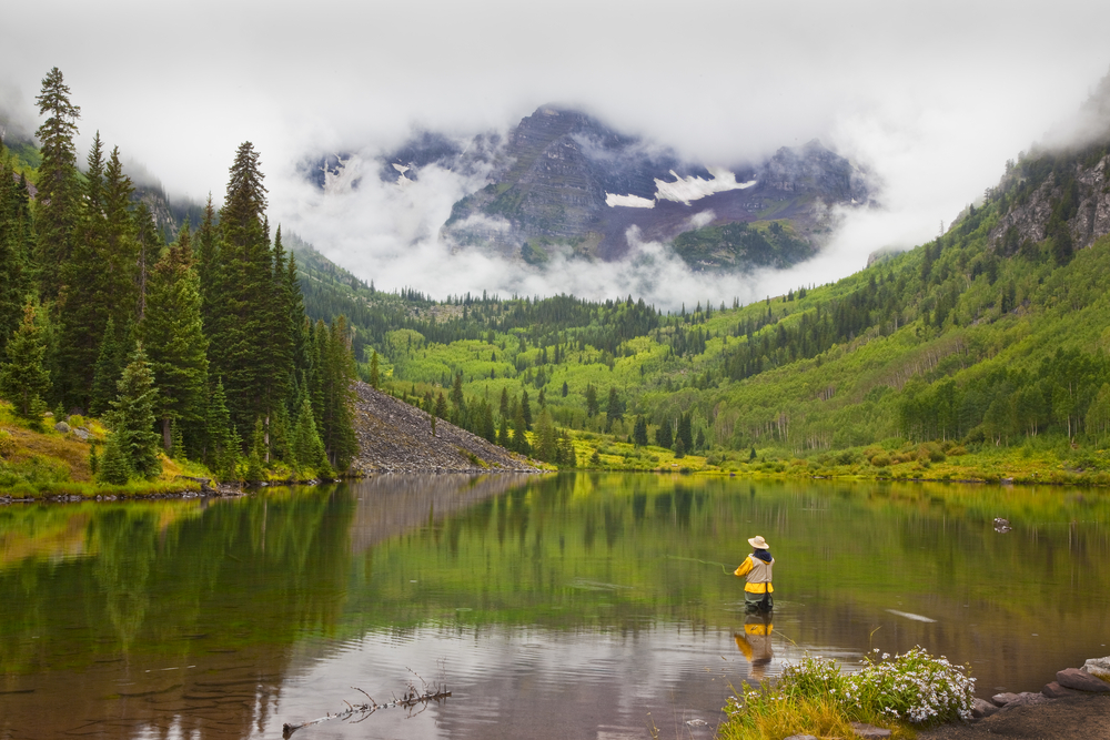 A person in a yellow jacket standing in a lake tosses a fly fishing line. The lake is surrounded by green trees, and clouds surround the distant mountains.