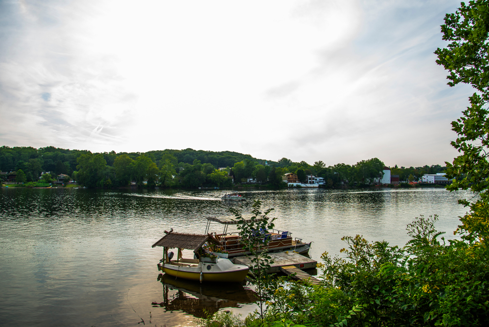 Two fishing boats docked at a sturdy wooden pier on the bank of a river. Other structures are seen on the opposite bank.