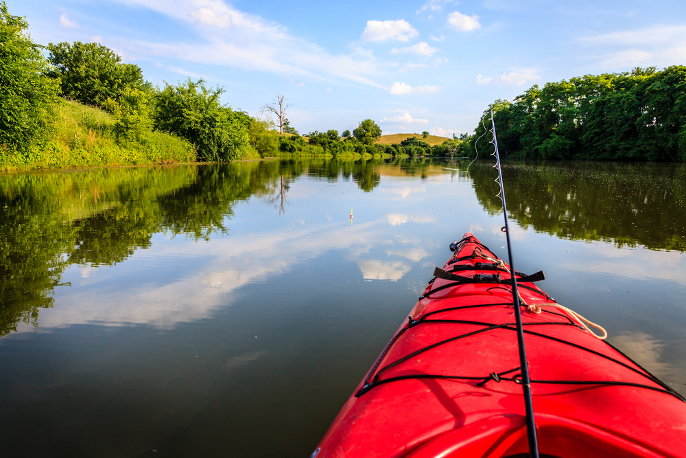 A fishing pole leans out of a red kayak on a calm lake surrounded by dense green trees.