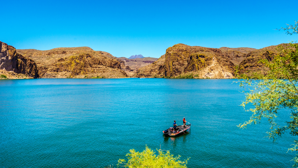 Two men stand, fishing, on a boat in the middle of a bright blue lake surrounded by rocky hills under a blue sky.