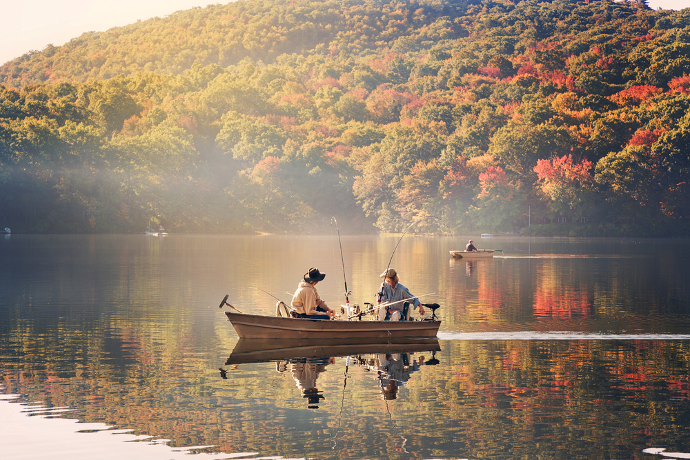 Two boats, one with two people and another with one person, sit on a calm lake, fishing. The bank is surrounded by dense forest.