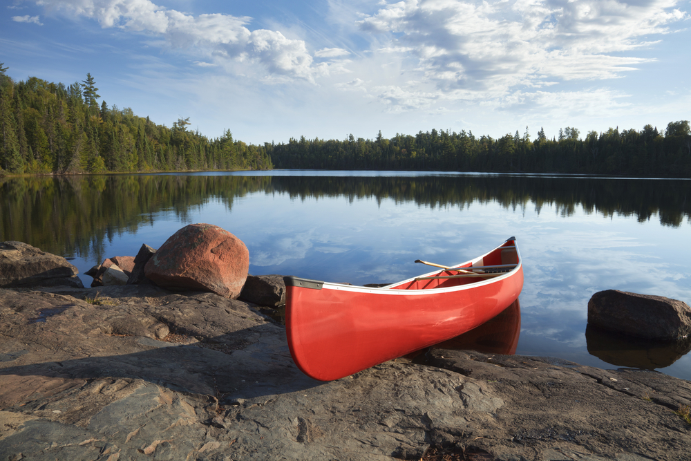 A red canoe on a rocky shore of a calm blue lake surrounded by trees under a wispy cloud-filled sky
