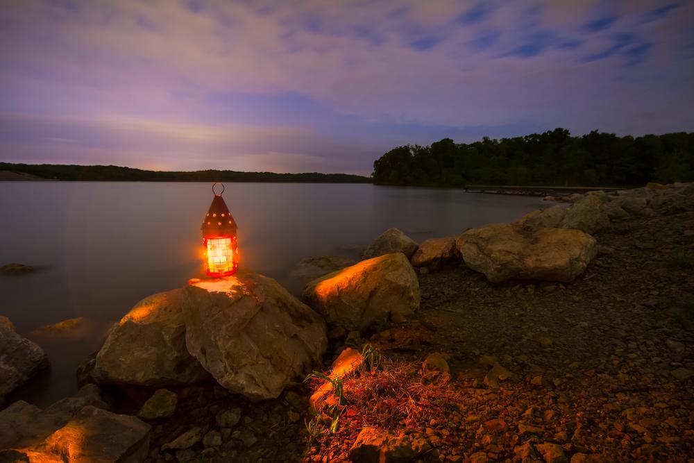 A lantern atop a large rock on a lake shoreline glows bright orange under a purple sky.