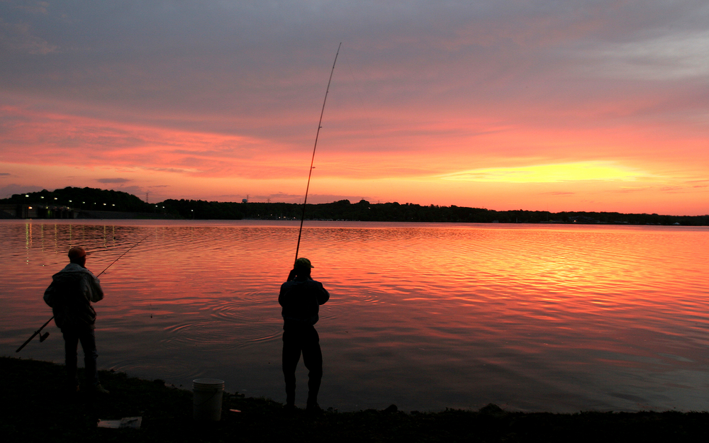 Two people with long fishing poles silhouetted on the shore of a lake, as the sun rises behind distant clouds.