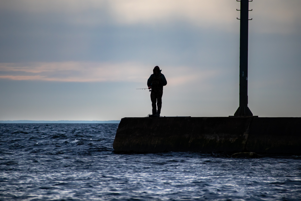 A silhouette of a fisherman fishing off a pier on a lake