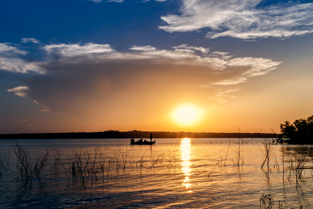 A man stands in the prow of a boat casting a fishing line. The boat is in the middle of a deep lake, and the sun is setting over the horizon.