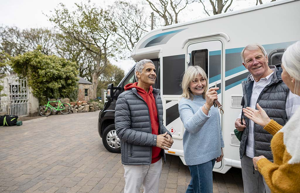 man and woman outside of an RV, woman holding keys