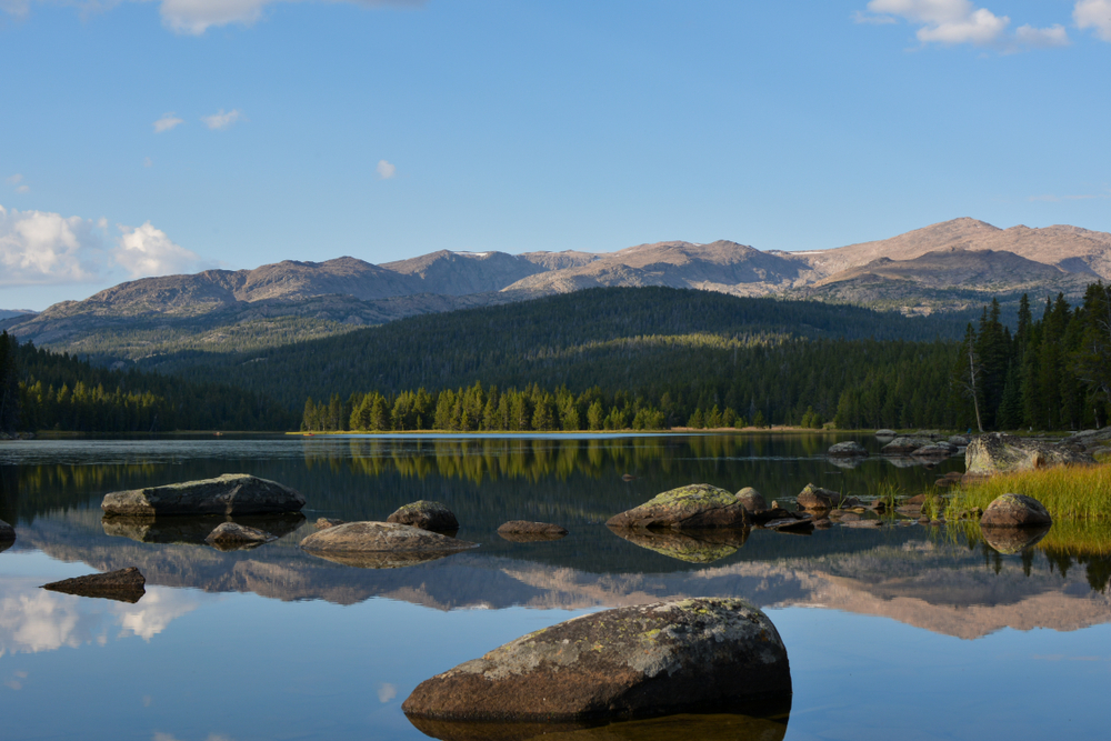A calm lake reflects a forested bank and tall mountains under a pale blue sky.